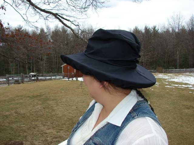 Boston Scarlet showing the black waterproof hat cover over her straw hat.
